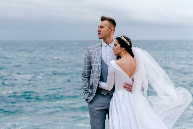 幸せな若いカップル、スーツを着た新郎、白いドレスを着た花嫁がベールを抱き締め、一方の側を見る