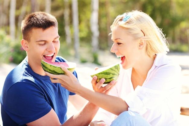 Молодая счастливая пара ест арбуз на пляже