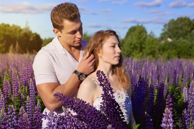Молодая счастливая пара в солнечный день в поле с яркими цветами