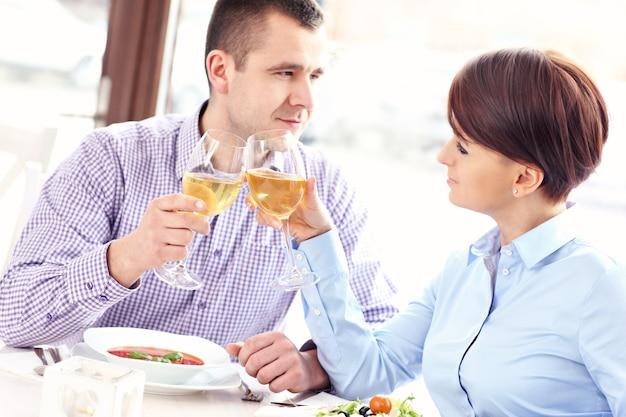 Молодая счастливая пара сидит в ресторане и пьет вино
