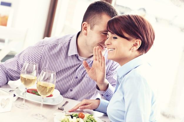 젊은 행복한 커플 레스토랑에 앉아 이야기