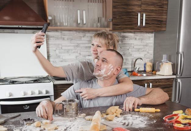 밀가루로 얼룩진 젊은 행복한 커플은 부엌에서 셀카를 걸립니다. 행복하고 사랑스러운 남편과 아내