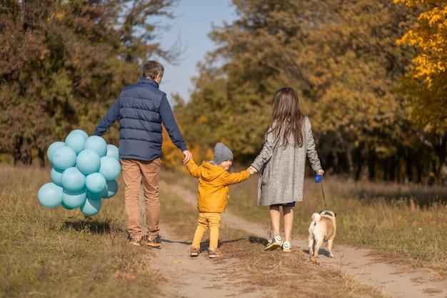 Молодая счастливая семья с маленьким ребенком и собакой с удовольствием проведет время вместе на прогулке в осеннем парке.