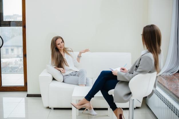 Молодая счастливая девушка общается с психологом в современном офисе