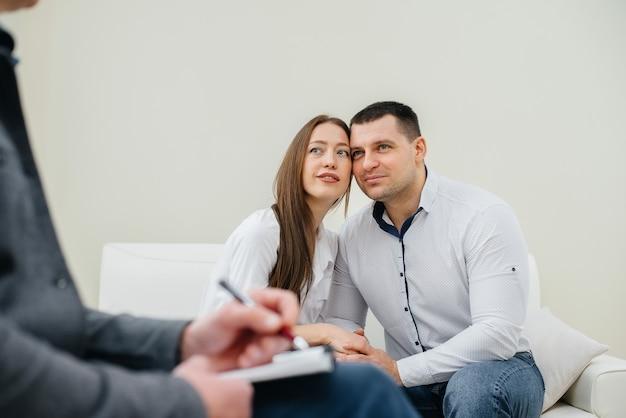 男性と女性の若い幸せな夫婦は、治療セッションで心理学者と話します。心理学。
