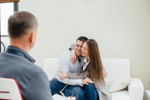 젊은 행복한 부부 남녀가 치료 세션에서 심리학자와 이야기합니다. 심리학.