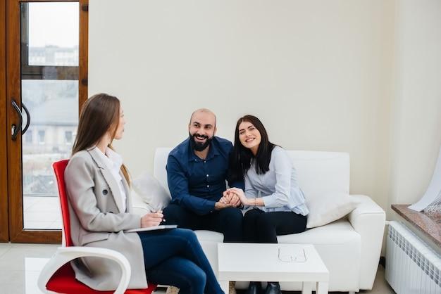 男性と女性の若い幸せな夫婦がセラピーセッションで心理学者と話します