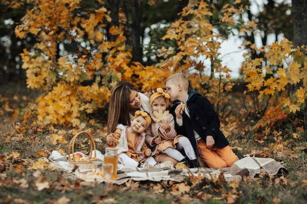 3人の小さな子供を持つ若い幸せな母親は、色とりどりの葉のある秋の公園でピクニックをしています。