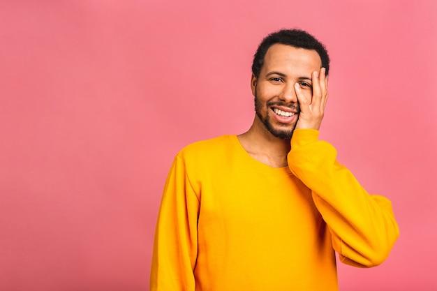 Молодой счастливый улыбающийся забавный человек, изолированных на розовом.