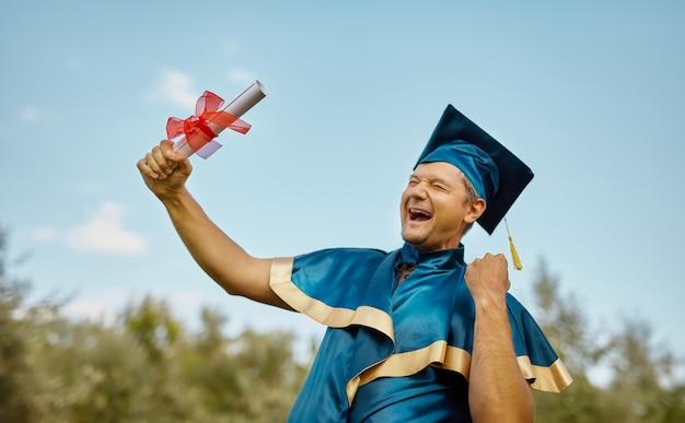 웃고 있는 젊은 남자가 푸른 하늘 위에 학위와 박사 학위를 수여합니다. 졸업 개념을 축하