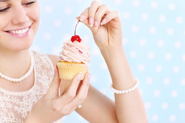 白と青の背景にカップケーキでポーズをとって若い幸せな女性