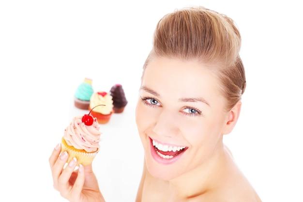 白い背景の上にカップケーキでポーズをとって若い幸せな女性