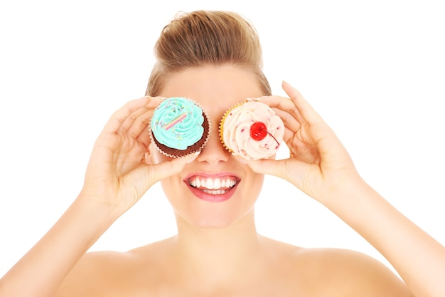 カップケーキでポーズをとる若い幸せな女性
