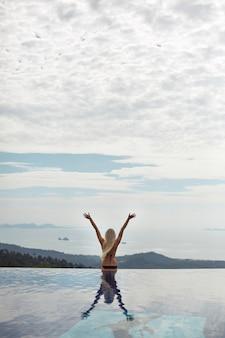 インフィニティプールの端に座って、旅行中に海を見ている若い幸せな女性...