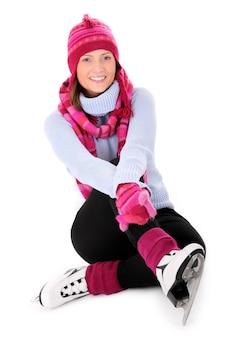 Молодая счастливая женщина сидит с коньками над белой