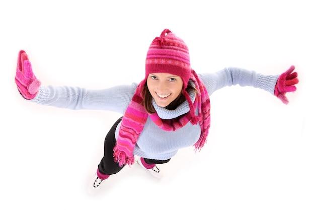 Молодая счастливая женщина катается на коньках над белой