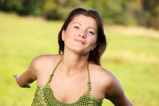 自然な緑の背景に笑みを浮かべて若い幸せな女性