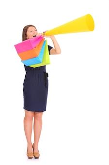 白であなたの製品を発表するメガホンを持つ若い幸せな女性