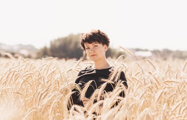 短い髪の若い幸せな女性が麦畑を歩く