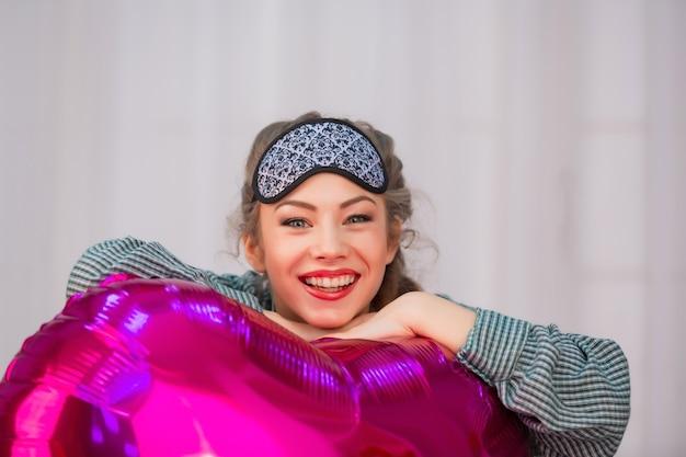수면 마스크의 젊은 건강한 소녀가 미소 짓고 심장 모양의 분홍색 풍선을 안아줍니다.
