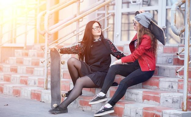 젊은 힙스터 소녀가 스케이트보드를 타고 있습니다. 스케이트보드를 타고 도시를 산책하는 여자 친구. 스케이트보드와 함께 거리에서 봄 스포츠.