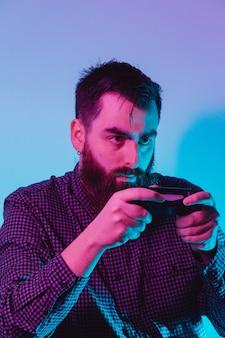 ピンクとブルーのライトで真面目な顔で遊んでいる間コンソールパッドを保持している若い流行に敏感な男