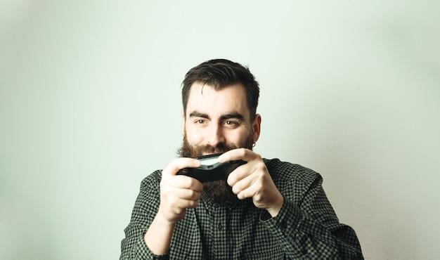 笑顔でコンソールパッドを保持している白い背景を持つ若い流行に敏感な男