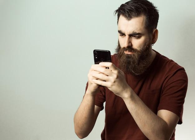 수염과 현대 헤어 스타일을 가진 젊은 힙 스터 스타일의 남자가 복사 공간이있는 자신의 전화 화면을 보면서 화가났습니다.