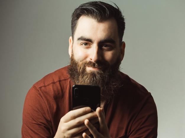 수염과 복사 공간이 자신의 전화 화면으로 카메라를 보면서 웃 고 현대적인 머리를 가진 젊은 힙 스터 스타일의 남자