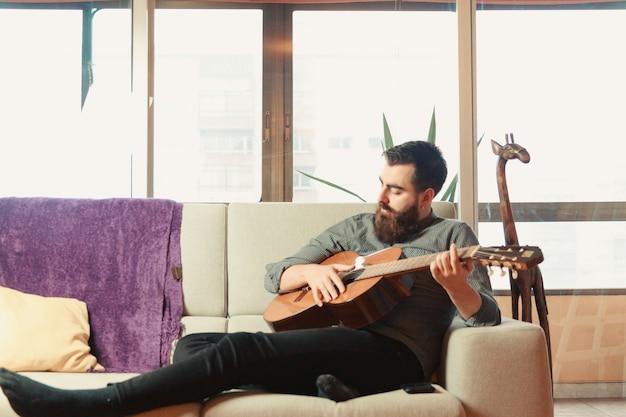 밝은 하루 동안 소파에 스페인 기타를 연주하는 수염과 셔츠 남성과 젊은 힙 스터