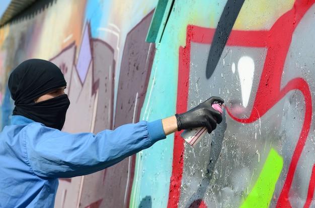 숨겨진 얼굴을 가진 젊은 훌리건은 금속 벽에 낙서를 그립니다.