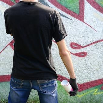 스프레이가있는 젊은 훌리건은 낙서 그림이있는 콘크리트 벽에 서 있습니다.