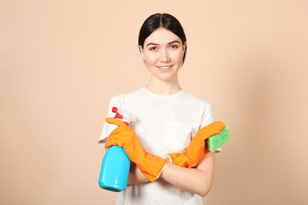 한 젊은 주부가 색색의 배경에 있는 청소 제품을 손에 들고 있다