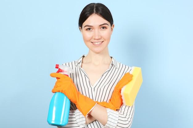 Молодая домохозяйка держит в руках чистящие средства на цветном фоне