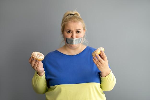 Молодая голодная пухленькая женщина с обиженным взглядом стоит с заклеенным ртом и держит в руках пончики.