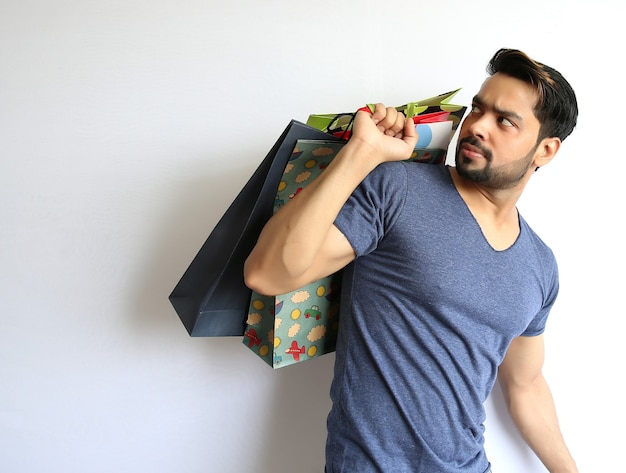 흰색 배경에 쇼핑백을 들고 젊은 인도 남자.