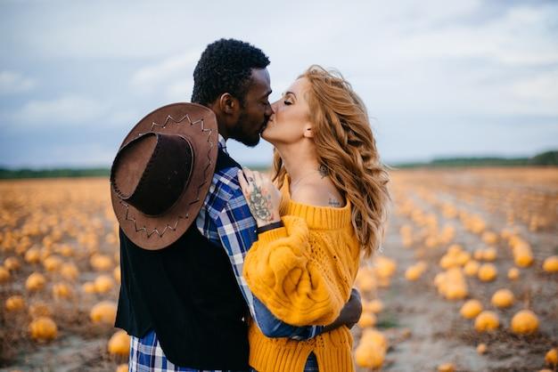 カボチャ畑でキスする若い異人種間のカップル
