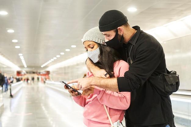 Молодая межрасовая пара влюбленных в масках и шерстяных шапках в коридоре метро