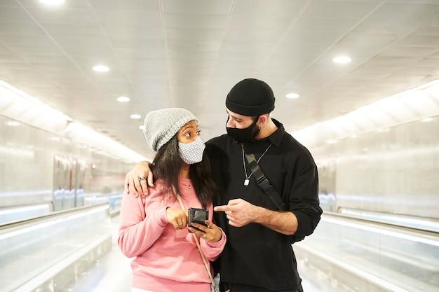 Молодая межрасовая пара влюбленных в масках и шерстяных шляпах идет по коридору метро