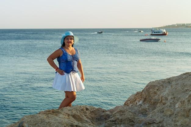 해변에 하얀 치마를 입고 태양 모자를 쓴 젊은 유대인 여성이 바위 위에 서 있습니다.