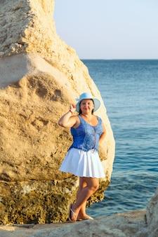 Молодая еврейка в белой юбке и синей шляпе на берегу моря у скал вертикаль