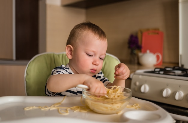 Молодой ребенок ест спагетти за высоким столом на кухне. учимся есть самостоятельно.