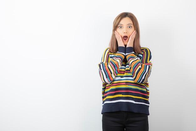 스웨터에 뺨 근처 손을 잡고 카메라를 찾고 젊은 아가씨.