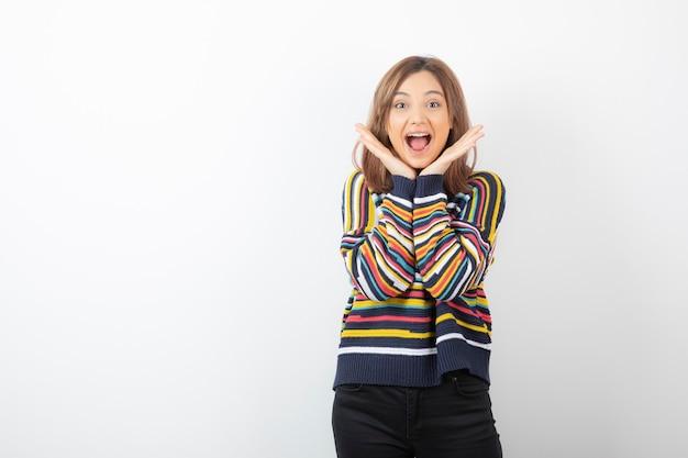 스웨터를 입은 뺨 근처에 손을 잡고 카메라를 바라보는 젊은 여성.