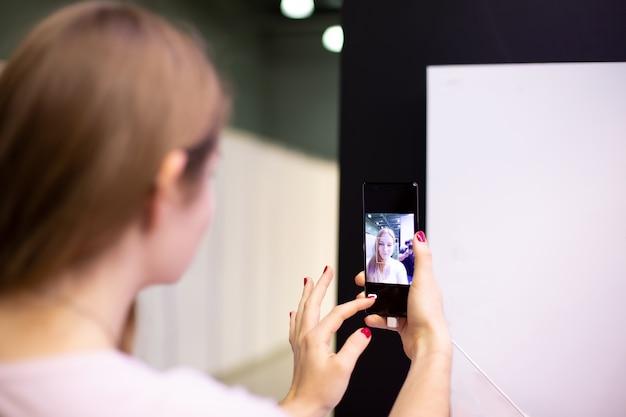 若い女性がsmatrphoneを持って、自分撮りをしている鏡のようにそれを調べます