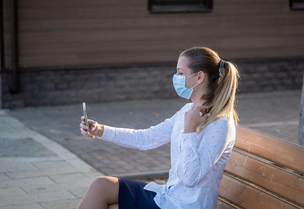 의료 마스크를 쓴 젊은 여성이 스마트 폰으로 셀카를 찍습니다. 코로나 19 유행 기간 동안 마스크 모드