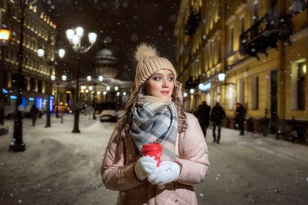 冬の夜に明かりの下でミトンと帽子の若い女性。サンクトペテルブルクのかわいい女の子の冬の肖像。一杯のコーヒーで美しいクリスマスの夜。