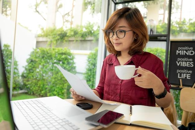 若い女性は紙を読んで、ラップトップでコーヒーカップを持っている