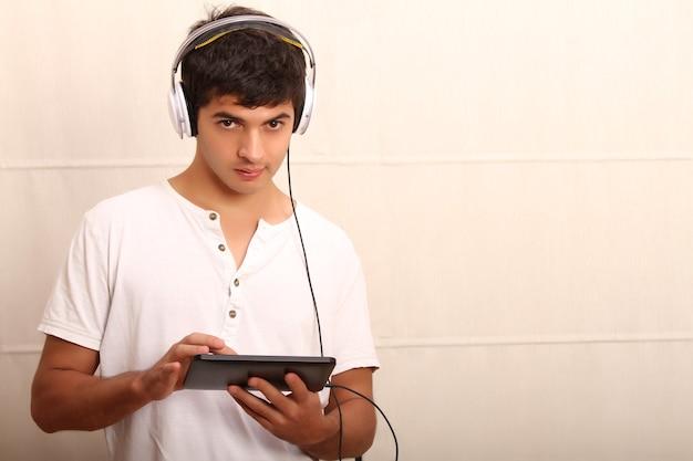 タブレットpcとヘッドフォンを持った若いラテン系男性