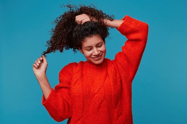 巻き毛の若いラテン系の女の子が手で髪を抱えて遊んでいる夢のように思慮深く頭を傾けて目を閉じた笑顔は青い壁に隔離された楽しい何かを想像します